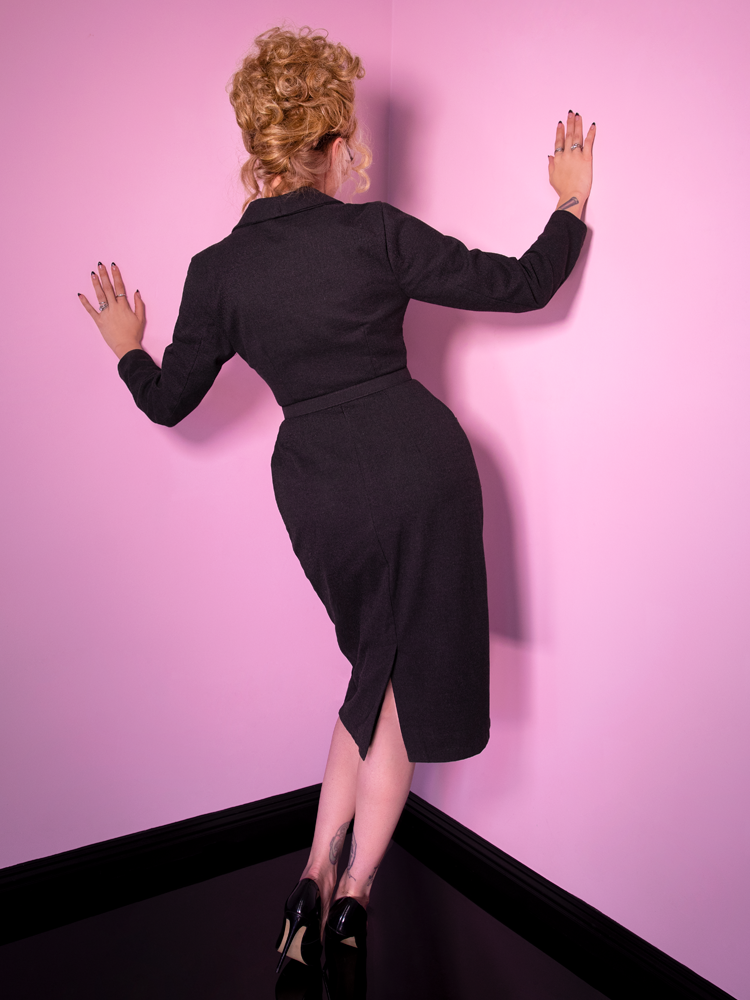 A back shot of Micheline Pitt wearing the Vixen Clothing Miss Kitty Secretary dress in dark grey.