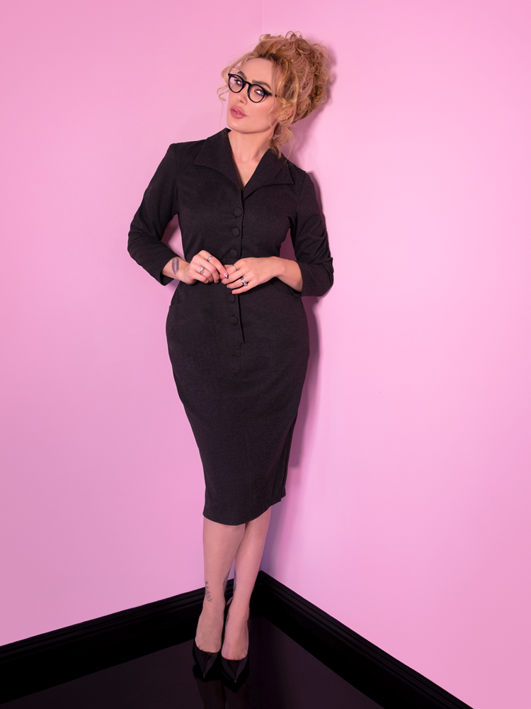 A full shot of Micheline Pitt wearing black rimmed glasses and looking at the camera wearing the Vixen Clothing Miss Kitty Secretary dress in dark grey.