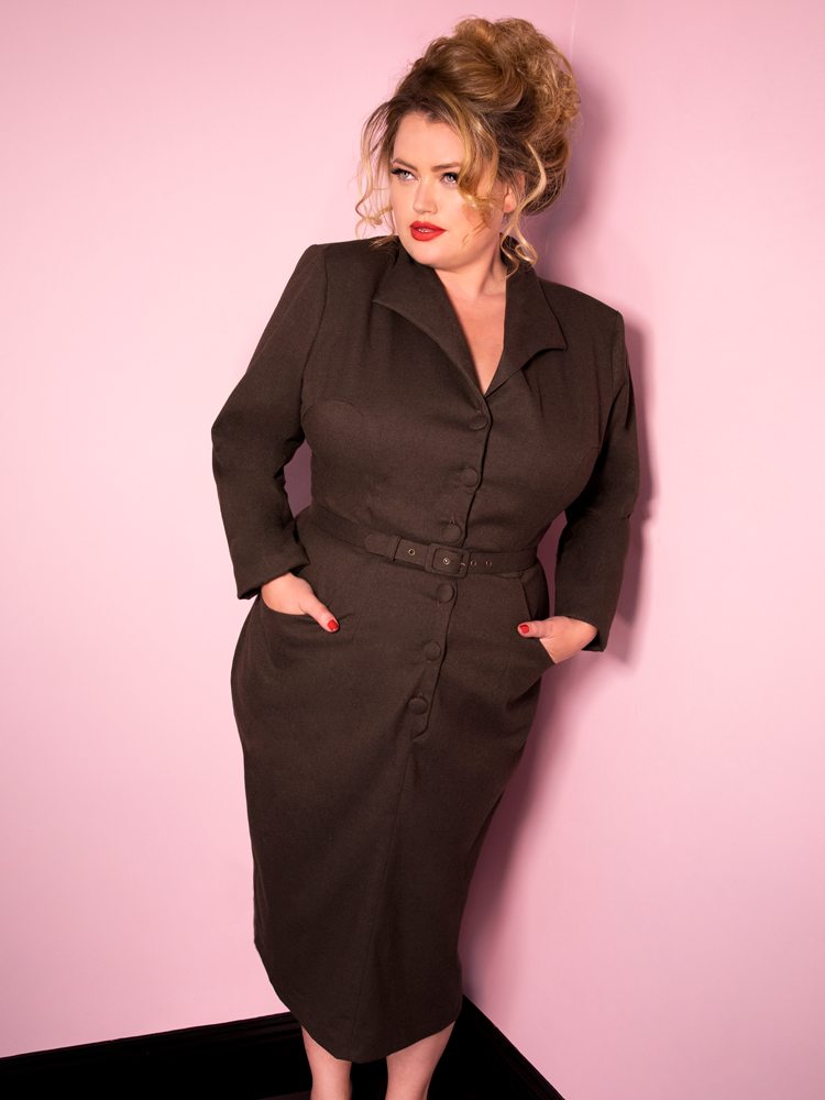 Blondie posing with her hands in the pockets of the Miss Kitty Secretary Dress in Brown from Vixen Clothing.