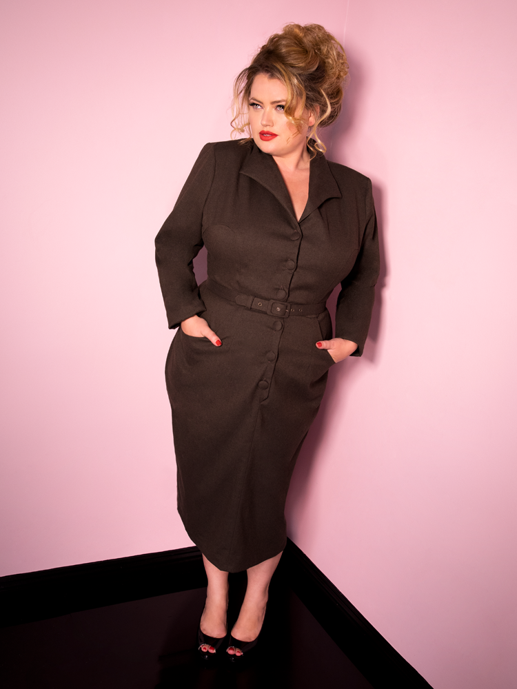 Full length shot of Blondie leaning against a wall wearing the Miss Kitty Secretary Dress in Brown from retro clothing company Vixen Clothing.