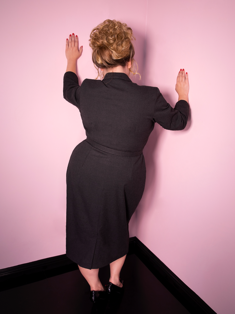 A back shot of Blondie modeling the Vixen Clothing Miss Kitty Secretary dress in dark grey.