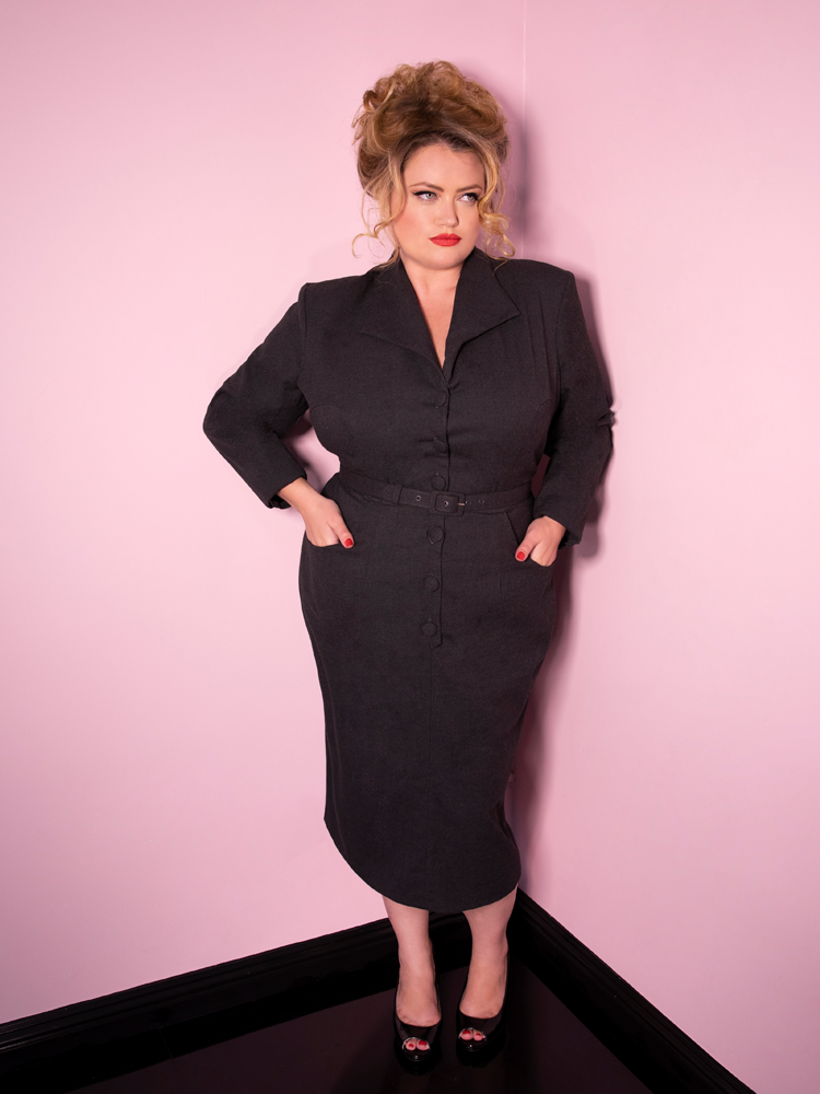 Blondie looking off camera with her hands in her pockets modeling the Vixen Clothing Miss Kitty Secretary dress in dark grey.