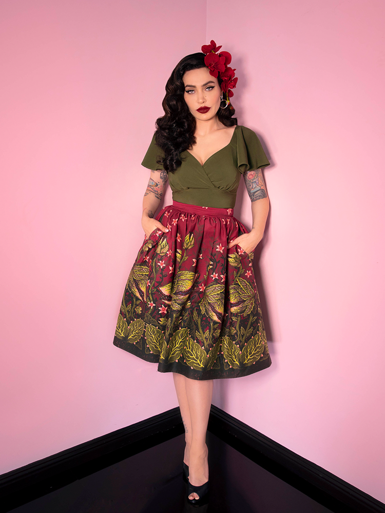 Full length shot of Micheline Pitt in olive green top and Vixen Swing Skirt in Maneating Monster Print.