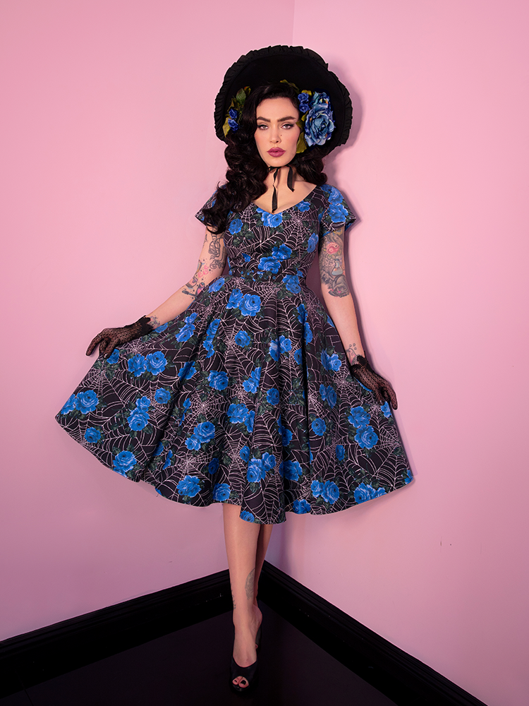 Wide-shot of Micheline Pitt wearing the Vanity Fair Dress in Blue Spider Web print from Vixen Clothing.