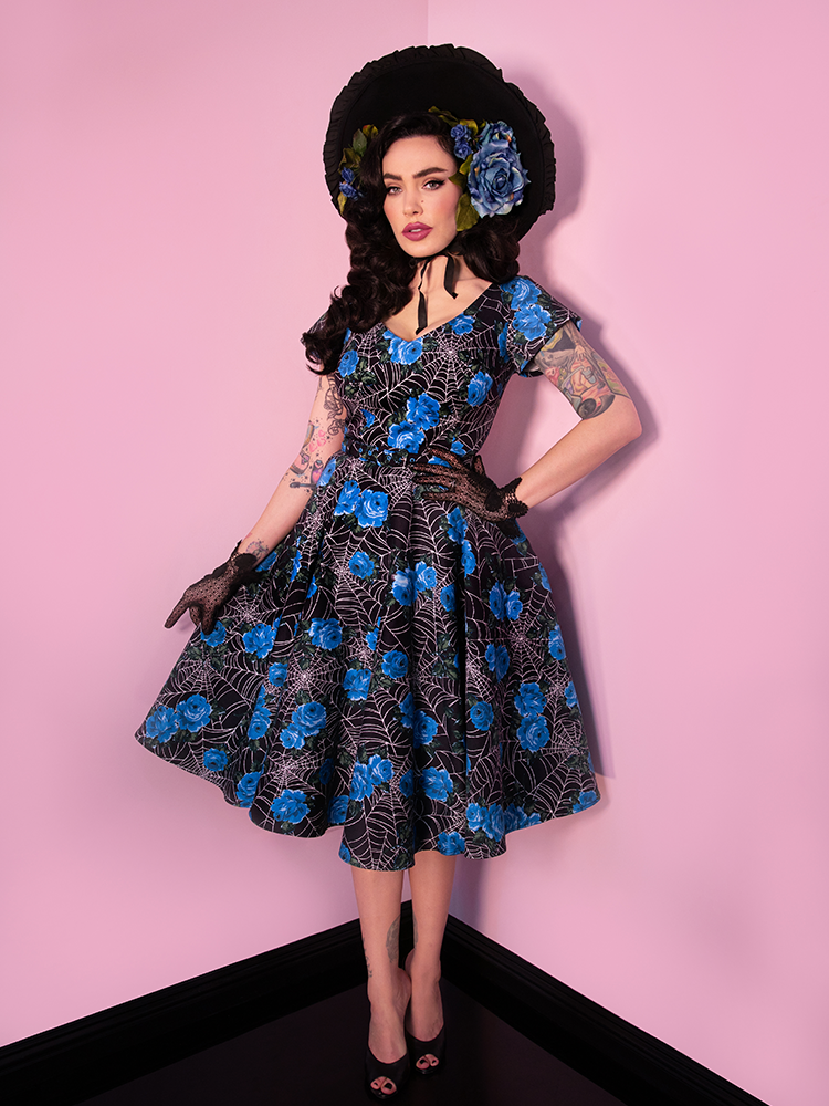 Micheline Pitt looking directly at the camera, modeling the Vanity Fair Dress in Blue Spider web.
