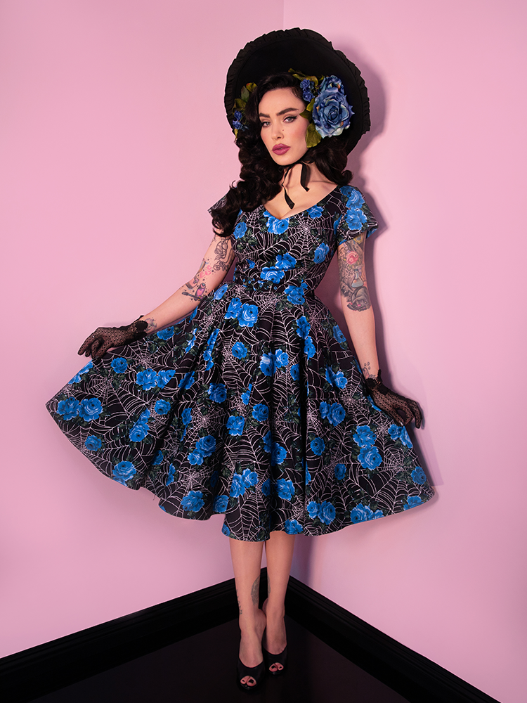 Black haired model showing off a retro inspired dress from Vixen Clothing that features blue roses and spiderwebs.