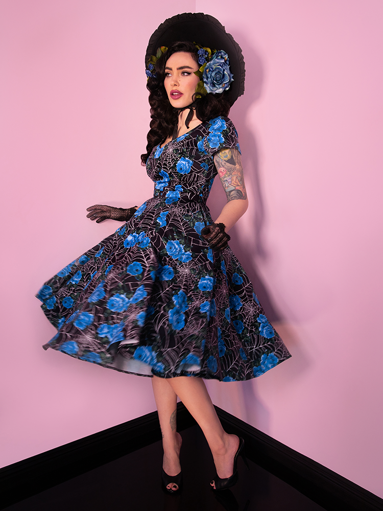Model and owner Micheline Pitt is caught in this shot mid-spin and wearing a retro inspired dress from Vixen Clothing.