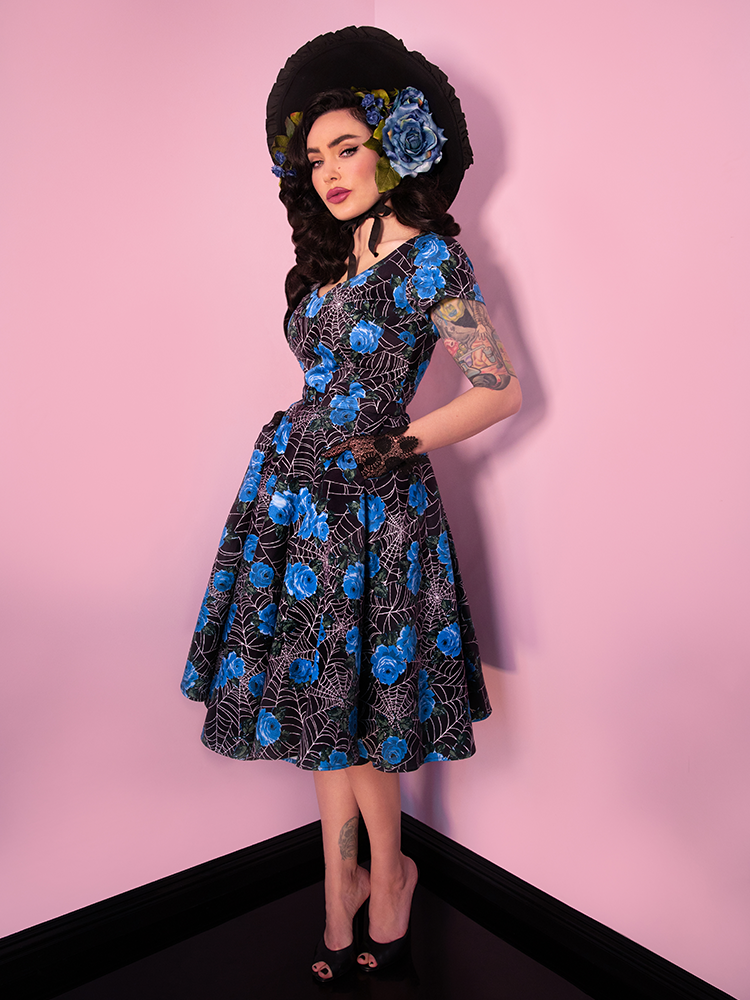 Posing with her hands on her hips, Micheline Pitt wearing the Vanity Fair Dress in Blue Spider Web print in addition to a black sunhat.