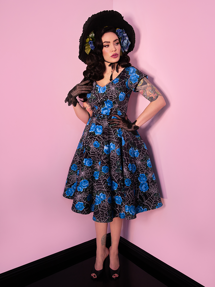 Black haired model with her hand on her hip, modeling a vintage style dress featuring a blue spider web print.