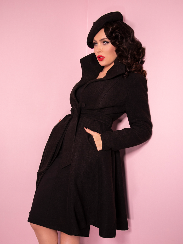 Looking like she stepped right off the screen of the latest James Bond movie, Micheline Pitt shows off the Starlet Swing Coat in Black from Vixen Clothing