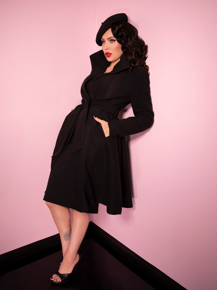 Full length shot of Micheline Pitt looking mysterious and stunning in the black Starlet Swing Coat and matching beret and shoes.