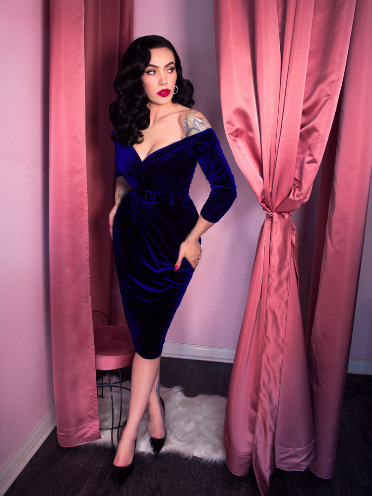 Standing in the entryway of a fitting room, Micheline Pitt places her hands on her hips and looks away from the camera while wearing a dark blue velvet wiggle dress from Vixen Clothing.