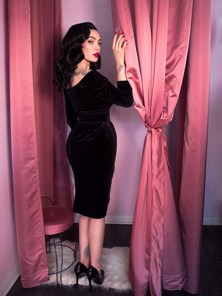 Back shot of Micheline Pitt wearing vintage style black dress