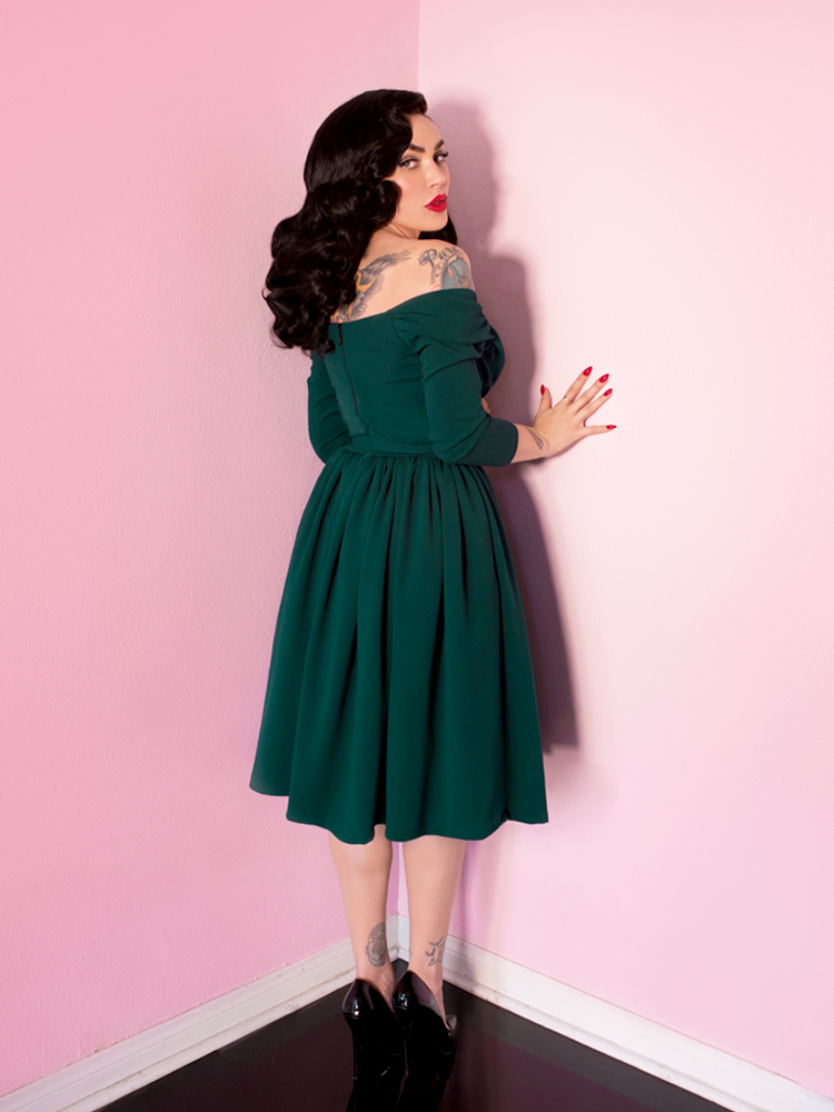 Micheline Pitt facing a wall while peering over her shoulder at the camera, sports a dark hunter green starlet swing dress from Vixen Clothing.