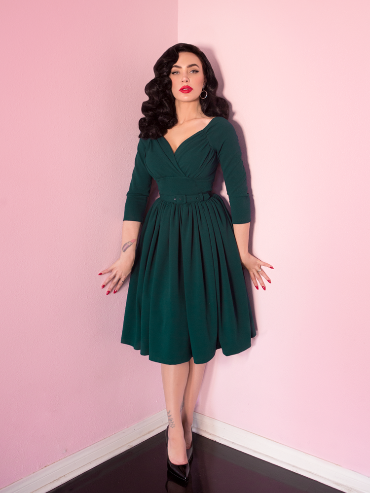 Model Michline Pitt slightly turning her head towards camera and modeling a Starlet Swing Dress in Hunter Green.
