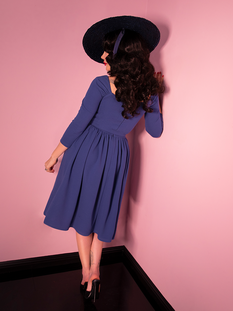 A back shot of Micheline Pitt looking off camera modeling the Starlet swing dress in stormy blue paired with a black straw sunhat.