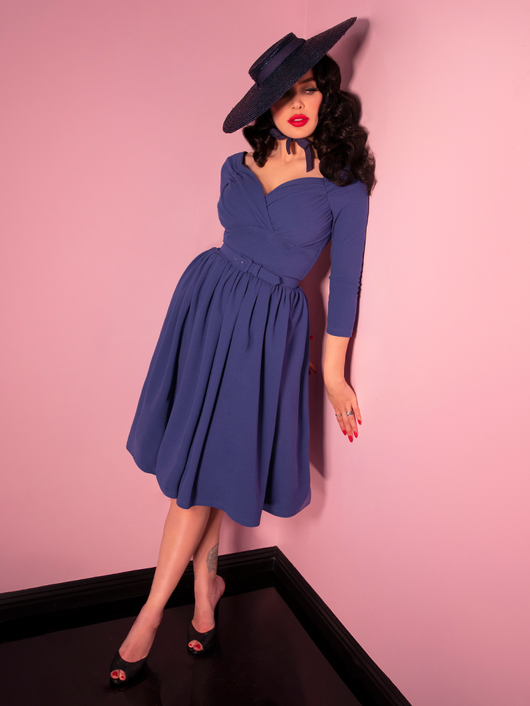 Micheline Pitt looking off camera leaning against a pink wall modeling the Starlet swing dress in stormy blue paired with a black straw sunhat.