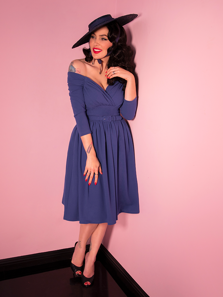 Micheline Pitt looking off camera and smiling modeling the Starlet swing dress in stormy blue paired with a black straw sunhat.