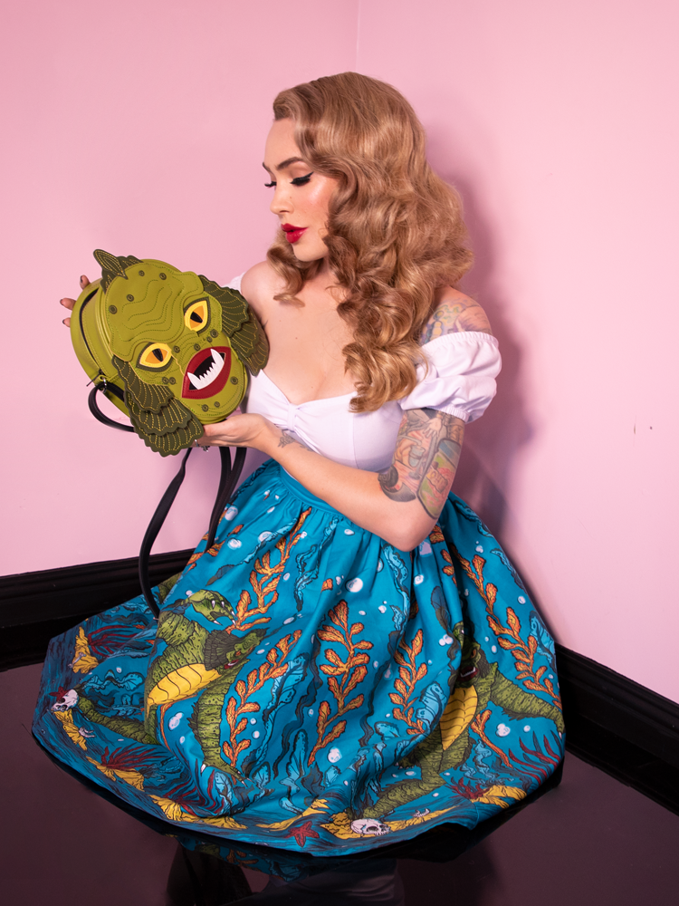 Gazing upon her Swamp Monster body bag lovingly, Micheline Pitt wears the Swing Skirt in Swamp Monster Print along with a white top down around her shoulders.