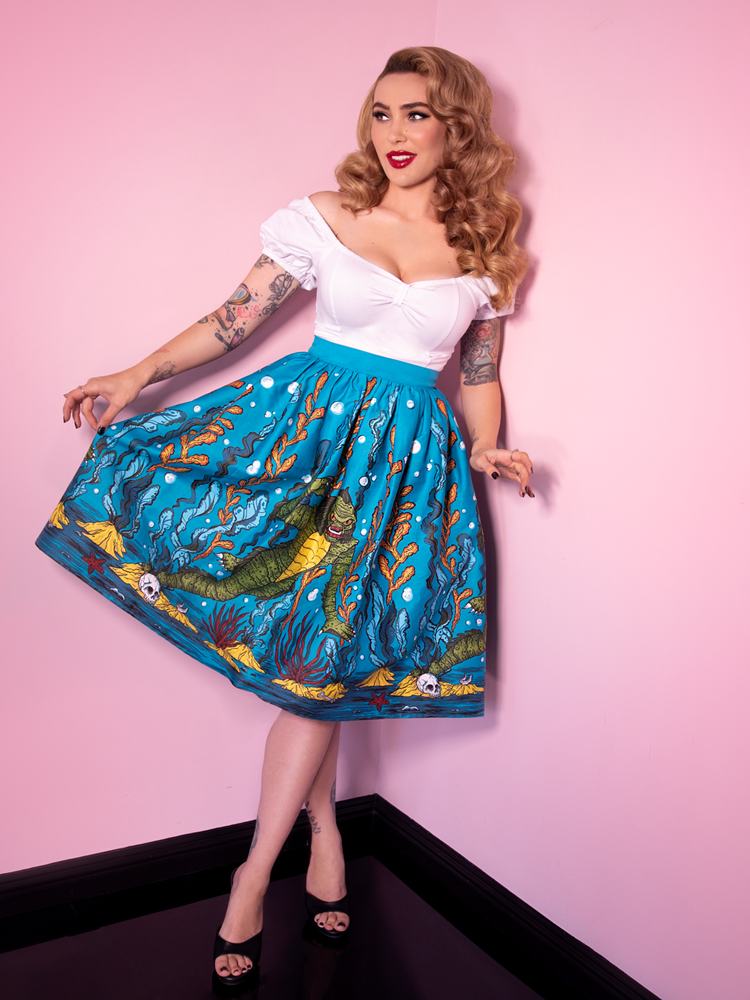 Full length body picture of Micheline Pitt wearing the Swamp Monster Swing Skirt from Vixen Clothing and holding out one side of the fabric to show off the intricate original artwork.