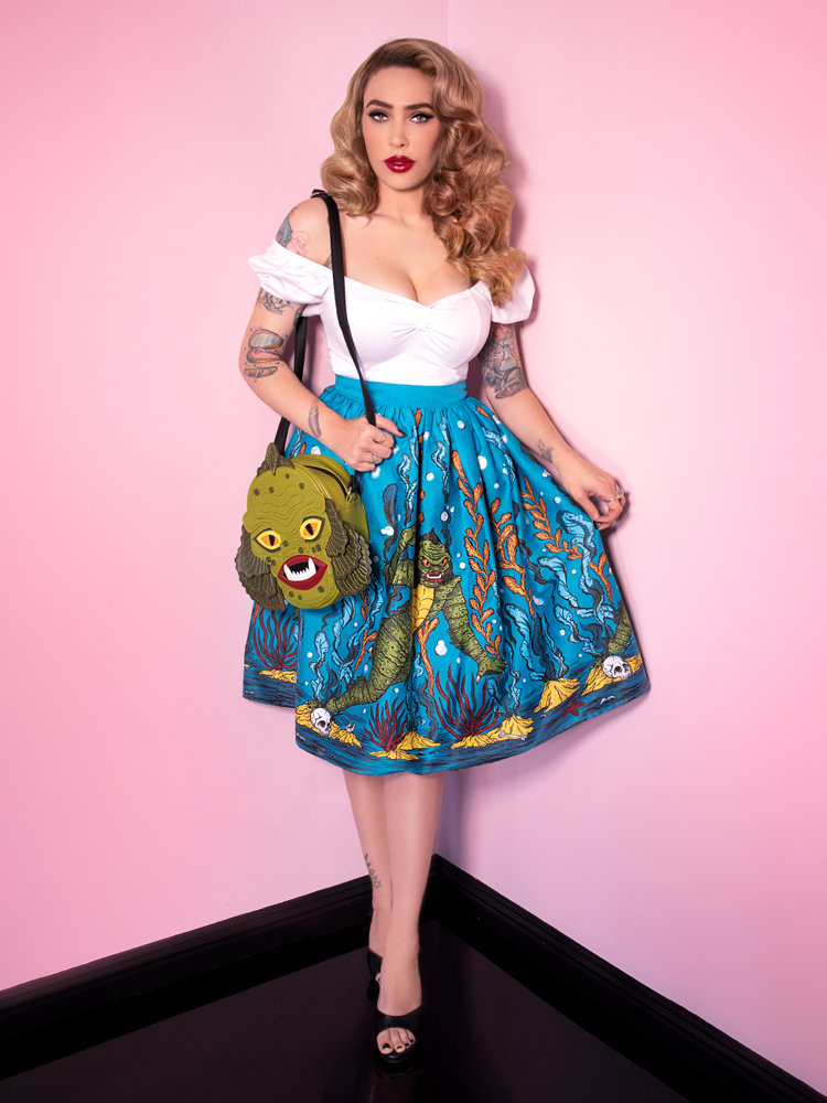 With her Swamp Monster body bag hanging off of her shoulder, Micheline Pitt looks straight at the camera while completing the look with the Vixen Swing Skirt in Swamp Monster Print from Vixen Clothing.