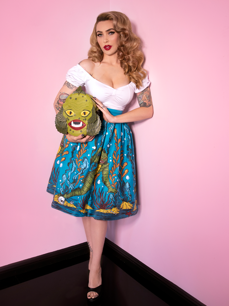 Showing off her intricately design Swamp Monster Body Bag, Micheline Pitt wears a vintage inspired skirt with the same character inspiration serving as design inspiration and a white top.
