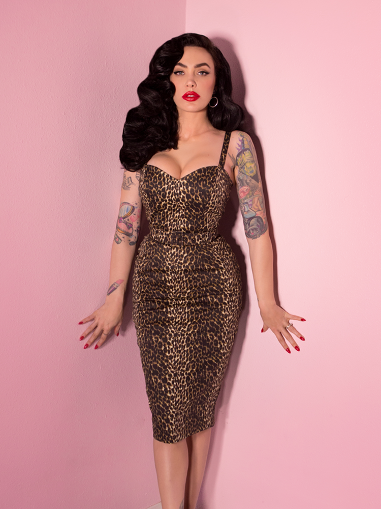 Micheline Pitt wearing a leopard print wiggle dress standing against a pink background.
