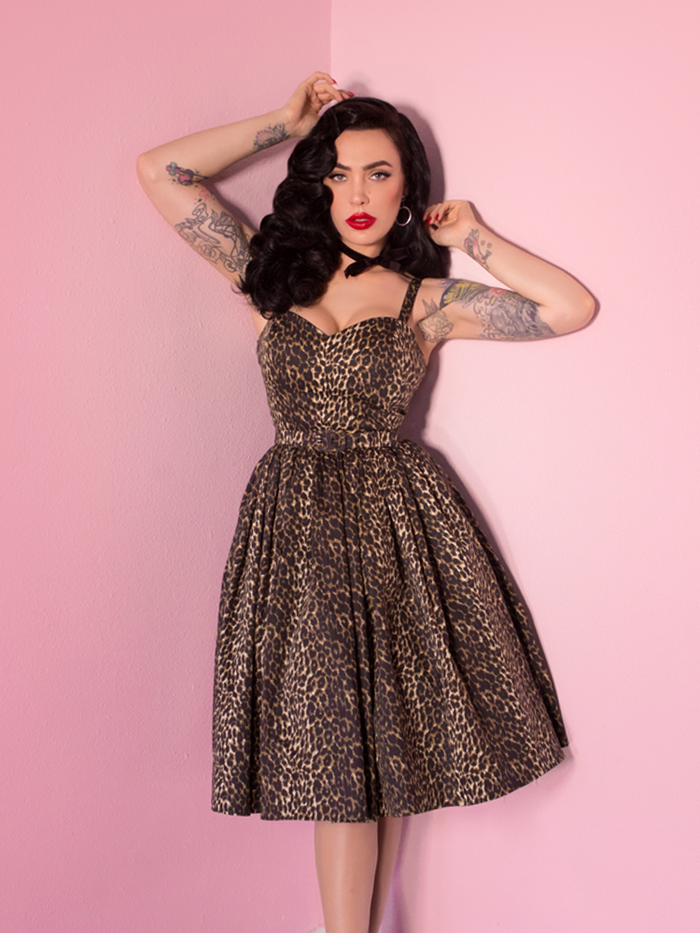 Micheline Pitt, raising her arms above her head, posing in a leopard print sweetheart swing dress.