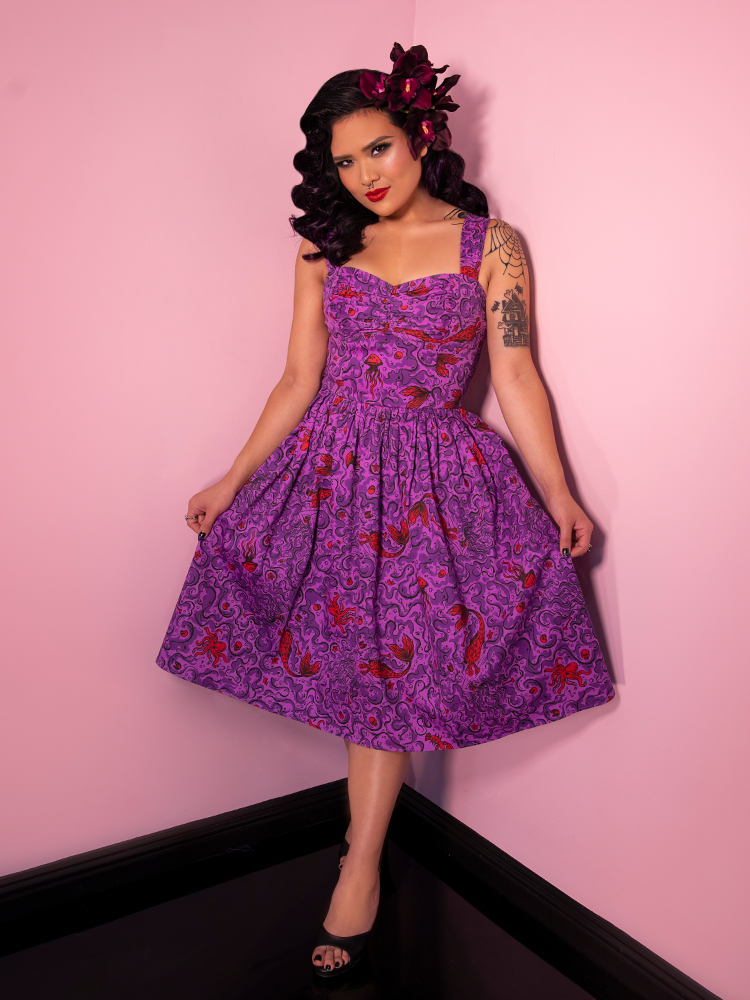 Model posing with swing dress in vintage inspired sea siren print.