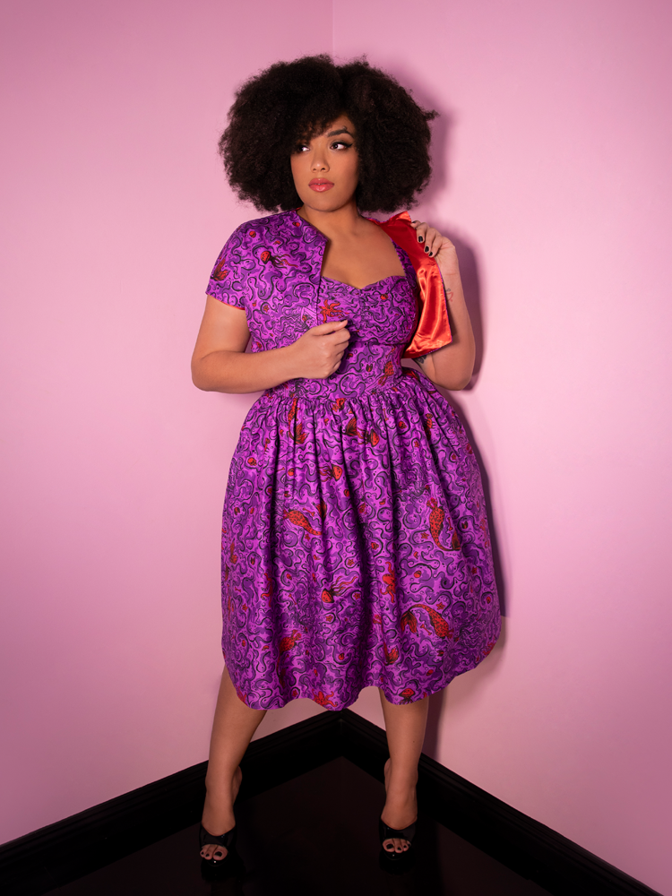 Ashleeta posing in a purple novelty print dress from Vixen Clothing.