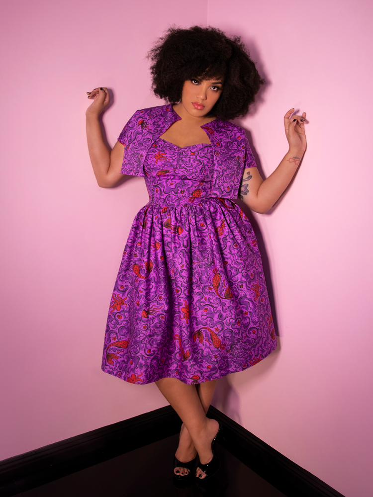 Full body shot of Ashleeta wearing a vintage inspired outfit from Vixen Clothing including purple dress in novelty print.