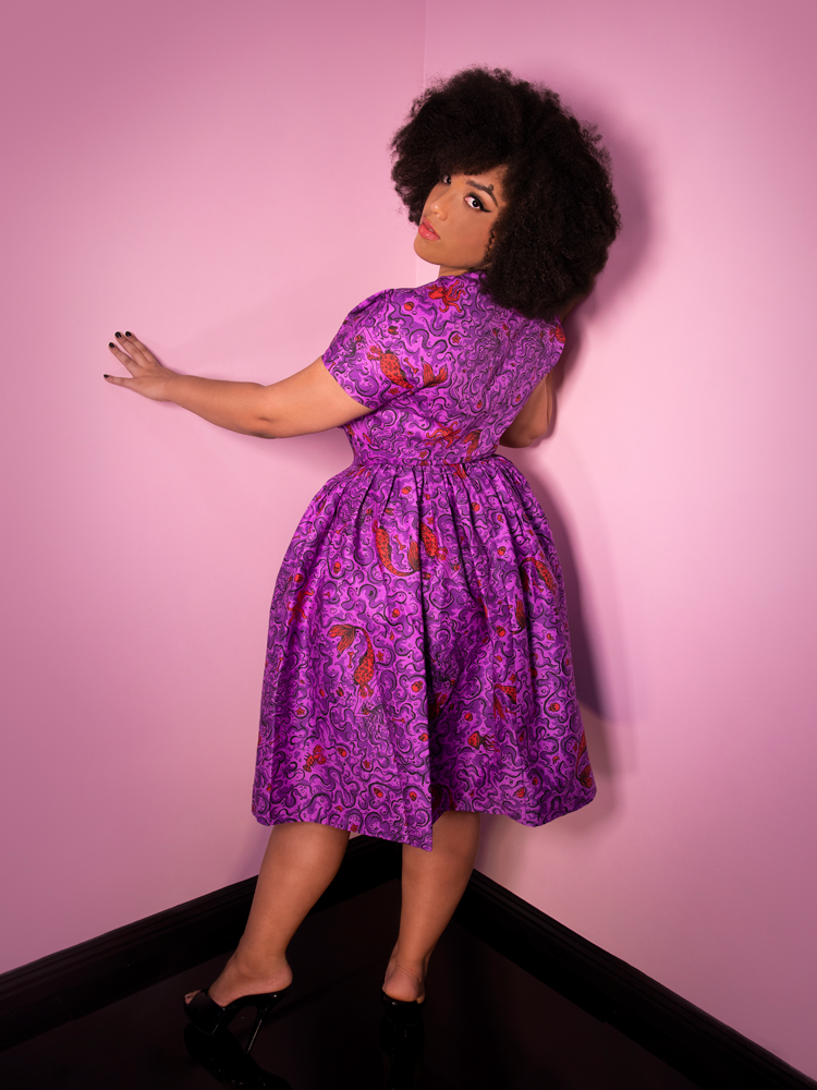 Ashleeta showing off the back of the Tropical Terror Swing Dress in Sea Siren Print from Vixen Clothing.