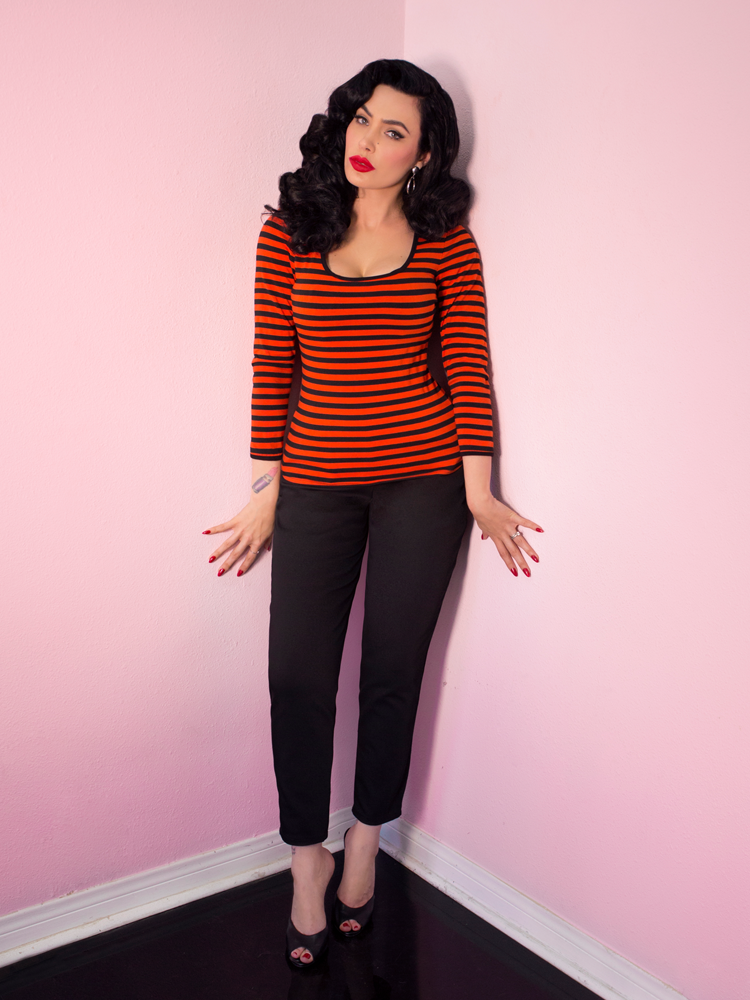A full length shot of Micheline Pitt modeling the Troublemaker top in orange and black stripes untucked by Vixen Clothing.