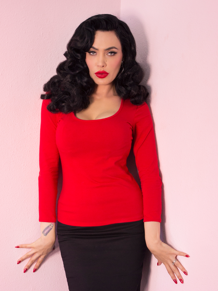 Micheline Pitt modeling the Troublemaker top in red untucked by Vixen Clothing.
