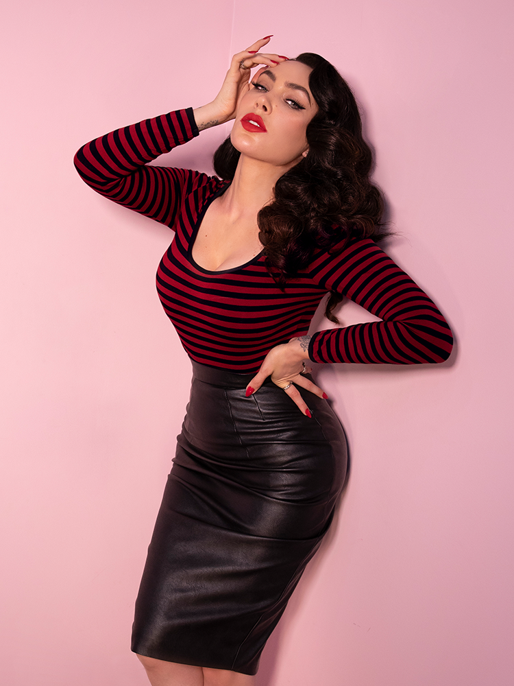 A retro inspired outfit from Vixen Clothing - dark red and black striped top paired with a vegan leather skirt being worn by Micheline Pitt.