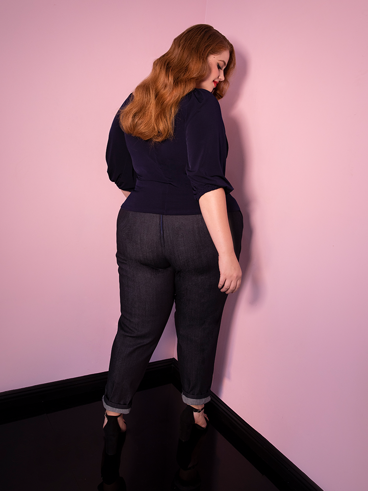 Bree turned away from the camera models the cigarette pants in denim from Vixen Clothing paired with a navy top.