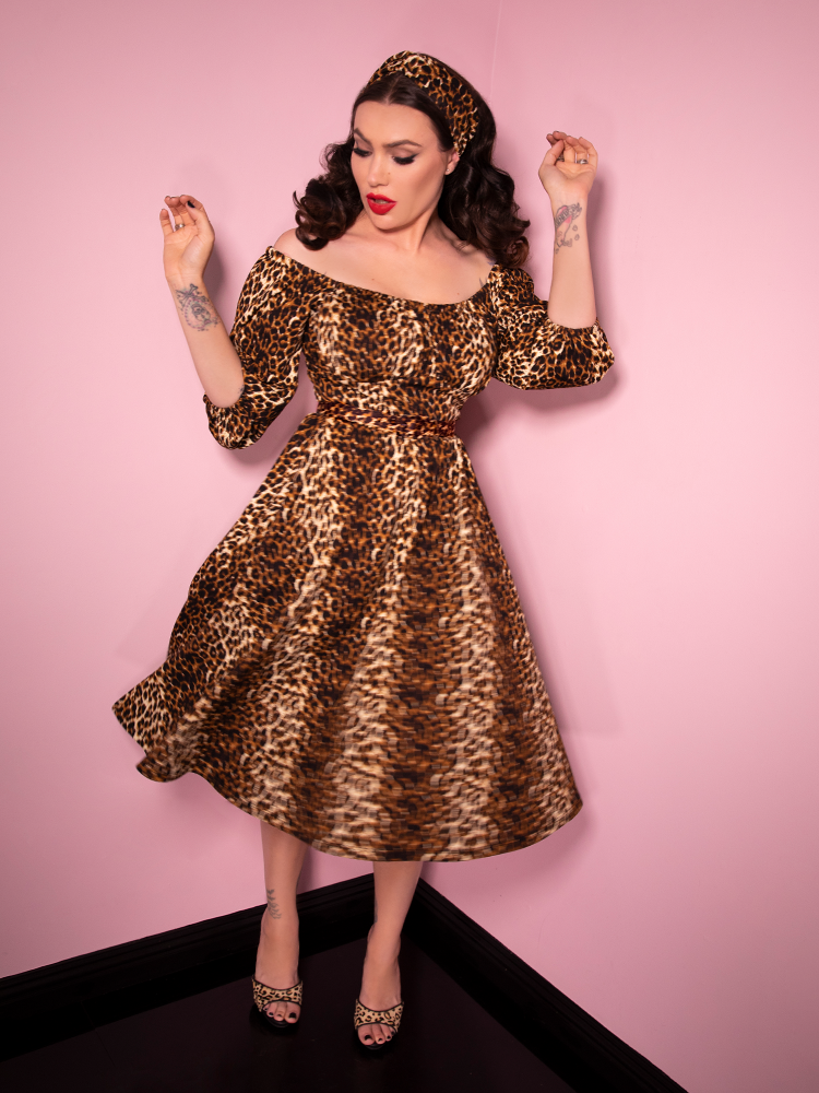 Micheline Pitt caught mid-spin in her Leopard Print Vacation Dress from Vixen Clothing.