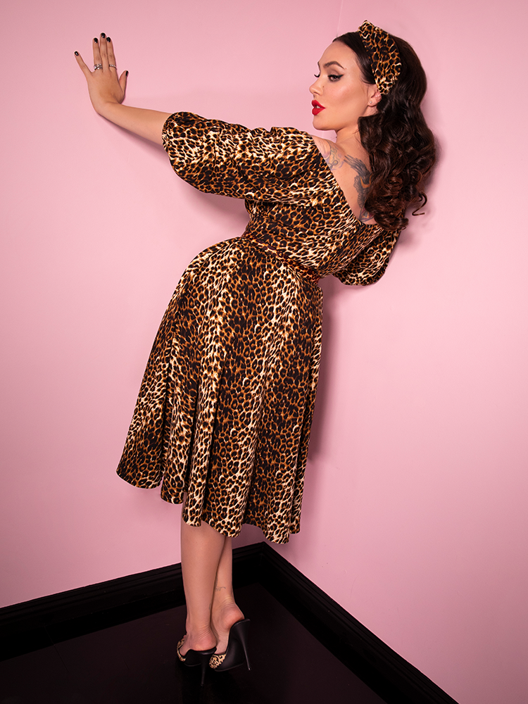 Bracing herself against the pink walls of the flagship Vixen store, Micheline Pitt wears the Vacation Dress in Vintage Leopard - a retro inspired masterpiece from Vixen Clothing!