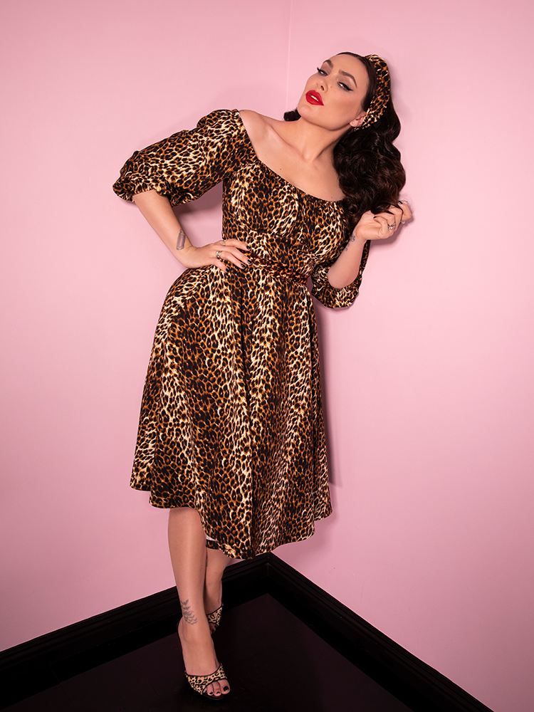 Leaning against a pink wall, Micheline Pitt models the Vacation Dress in Leopard Print from Vixen Clothing.