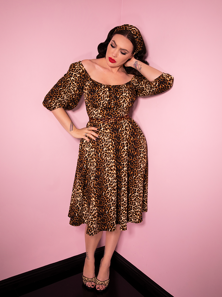 Micheline Pitt standing against pink painted walls and wearing the Vacation Dress in Vintage Leopard Print from Vixen Clothing.