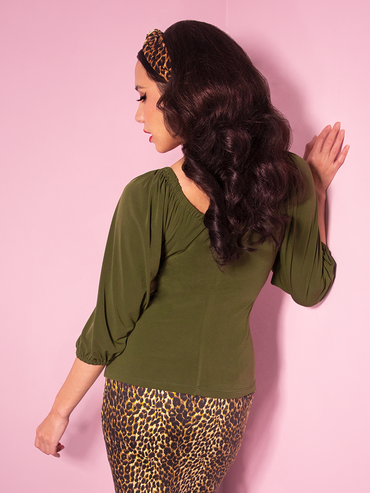Brunette model wearing a long sleeve olive green top along with pencil skirt in leopard print.