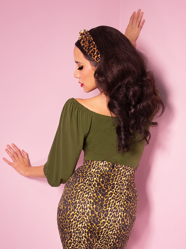 Back shot of Milynn in the Vacation Blouse in Olive Green from Vixen Clothing. Also pictured is the leopard print pencil skirt also from Vixen.