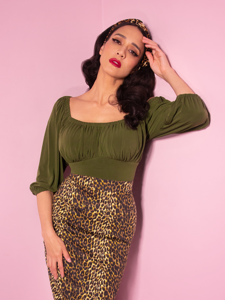 With her left hand touching her temple, Milynn looks like a damsel in distress while wearing the Vacation Blouse in Olive Green paired with a leopard print pencil skirt from Vixen Clothing.