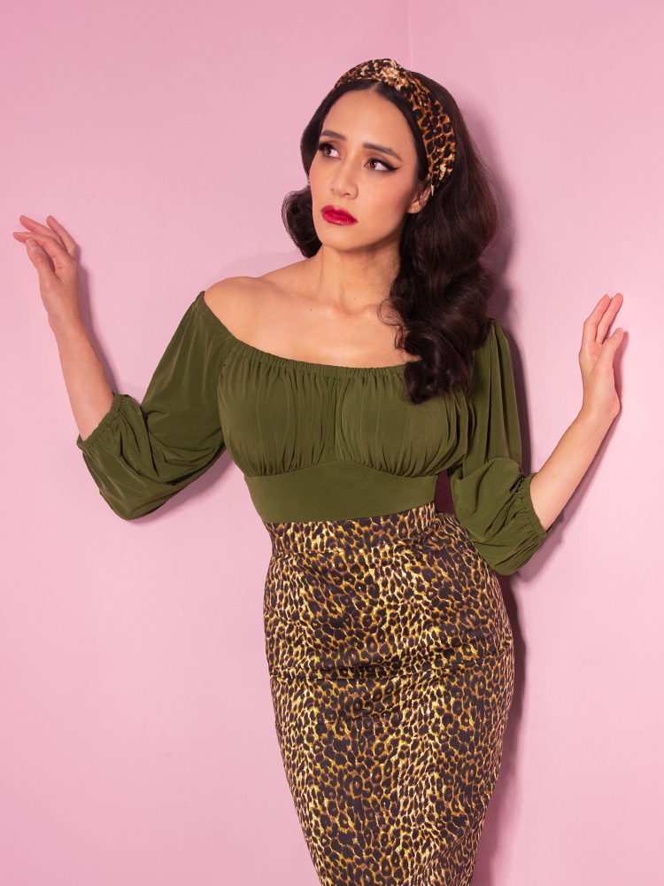 Model Milynn looking up and away from the camera while wearing an olive green blouse and leopard print pencil skirt from Vixen Clothing.
