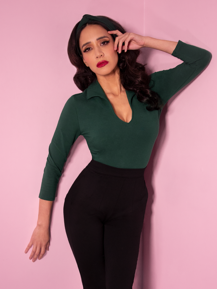 Milynn, with her hand on her face, modeling the Vixen top in hunter green paired with black vintage style pants.