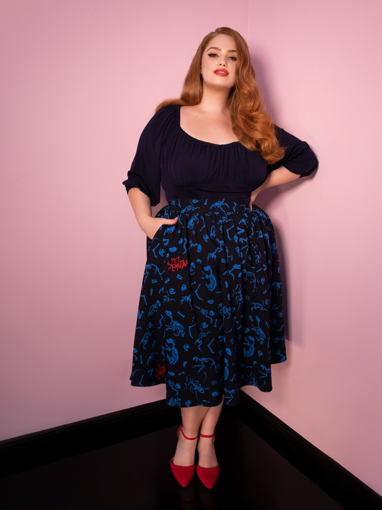 Model Bree stands with one hand in her pocket and the other on her hip, while smiling at the camera and wearing a navy blue top and retro swing skirt from Vixen Clothing.