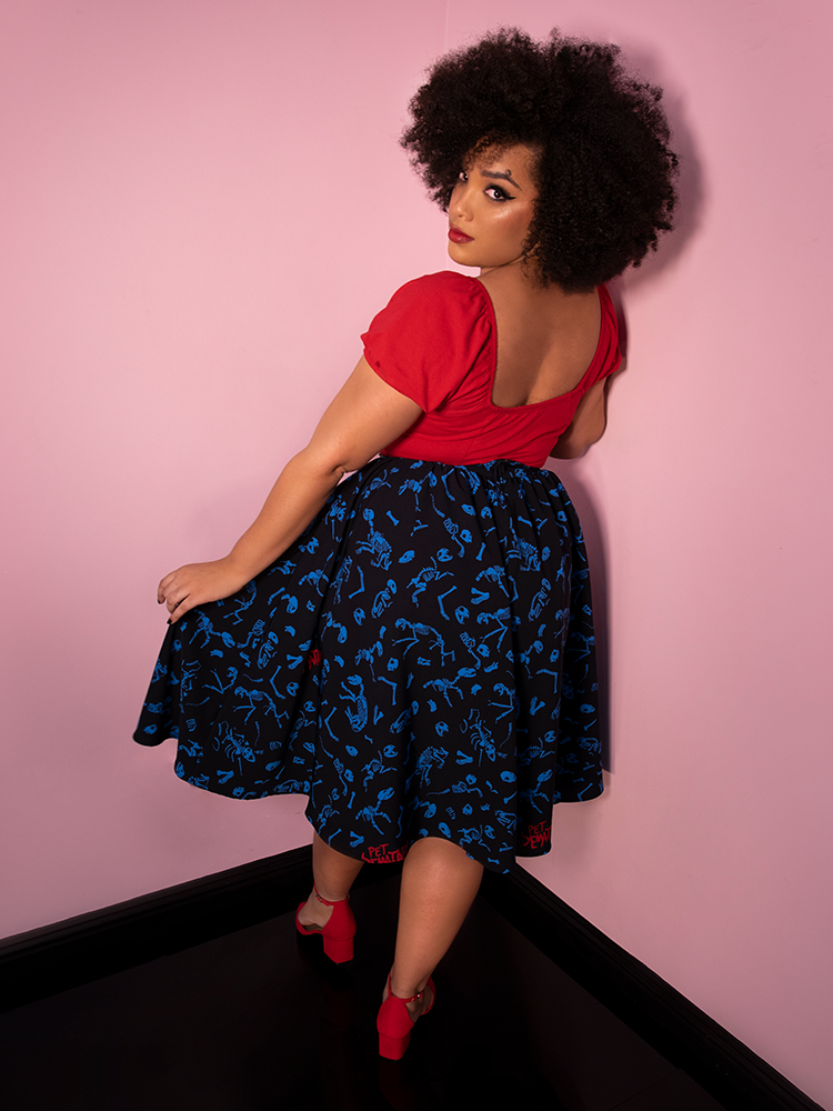 Model Ashleeta looks back over her shoulder at the camera while weaing the Pet Sematary Vacation Swing Skirt in Better Off Dead Print.