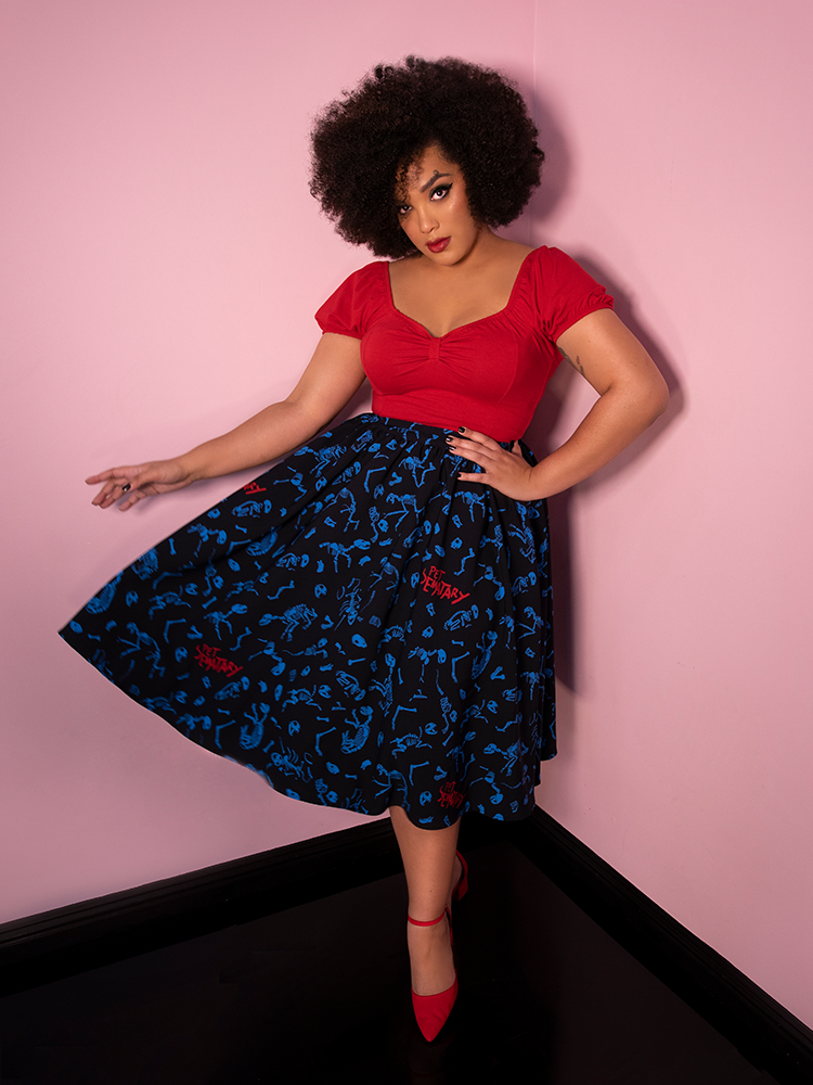Ashleeta is mid-twirl in a red top and Pet Sematary Vacation Swing Skirt - a retro clothing lovers' dream!
