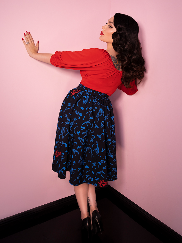 Micheline Pitt facing the wall and peering back over her shoulder, wearing the Pet Sematary Vacation Swing Skirt in Better Off Dead Print.
