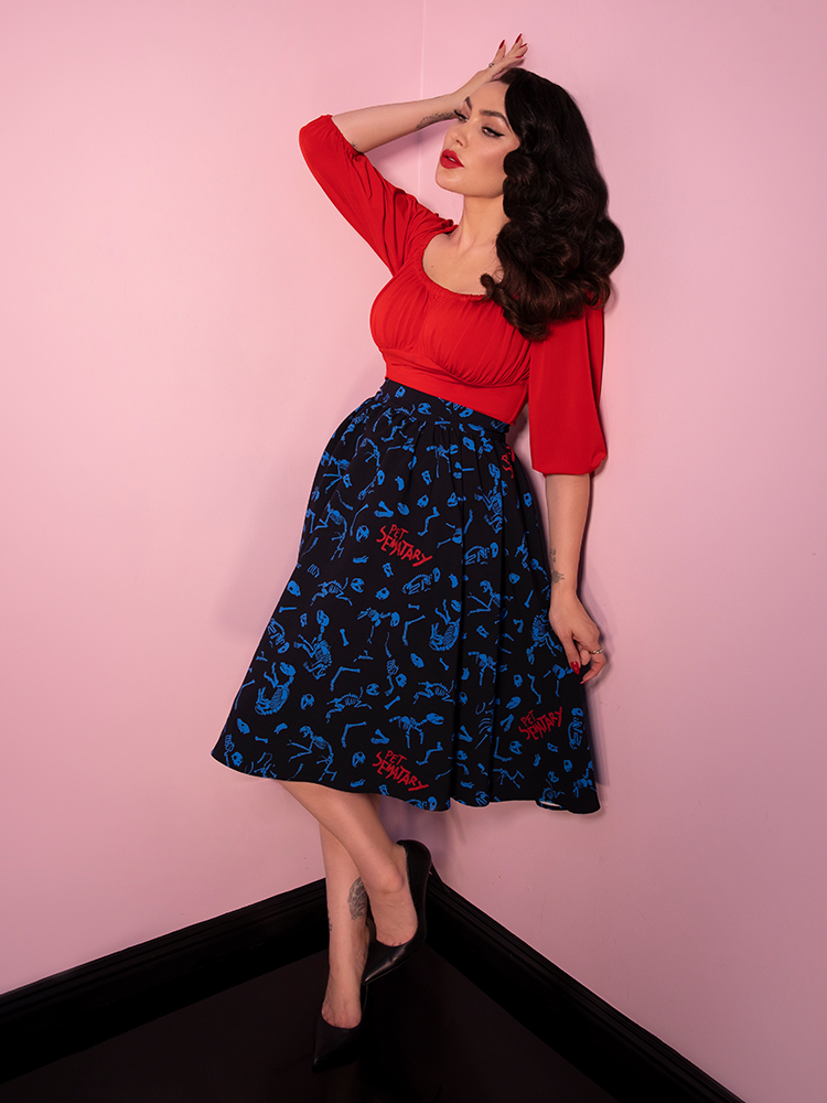 Full body shot of Micheline Pitt wearing a black vintage style skirt and a red longsleeve peasant top.